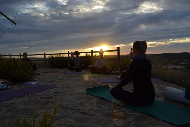 Yoga bij zonsondergang op vakantie in Spanje